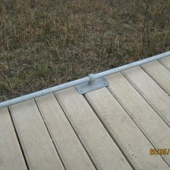 Galvanised steel kerb attached to concrete boardwalk.